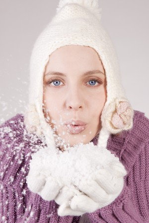 Young woman in soft sweater, cap and mittens, blowing powdery snow into the air photo