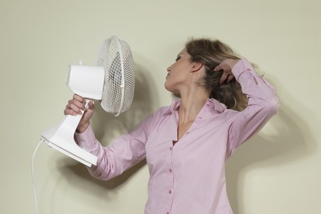 hot pink: Woman using a fan to cool off Stock Photo