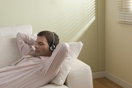 Young man listening to music on the couch photo