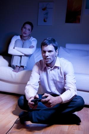 mujer decepcionada: Hombre jugando videojuegos, mujer decepcionado y aburrido