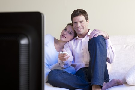 Relaxed couple watching TV, selective focus photo