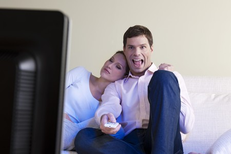 Man exulting watching TV, woman sleeping photo