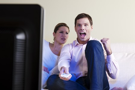 Man exulting watching tv, woman disappointed Stock Photo - 7471282