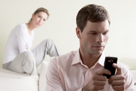 Jealous  woman looking at her partner chatting on the phone photo