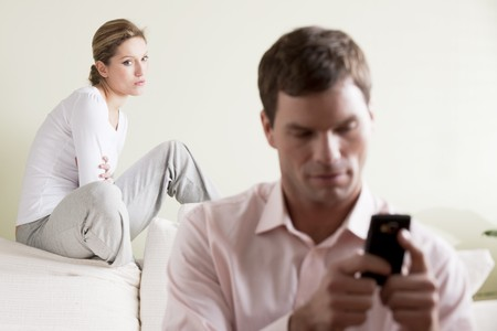 envy: Jealous  woman looking at her partner chatting on the phone Stock Photo