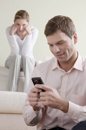 Femme jalouse regarder son partenaire conversation sur le téléphone