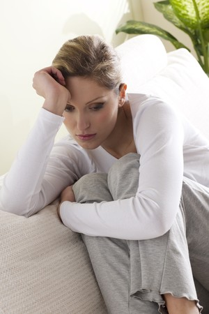 Sad/worried woman on her sofa Stock Photo - 7471378