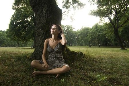 under a tree: Pure, natural, beautiful young woman in nature, sitting under a tree. Concept: teenagers and nature