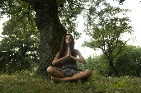 Young woman holding her hands against her chest and meditating in nature. Taken in Lipica, Slovenia. Concept: teenagers and nature, spiritual teenagers. photo