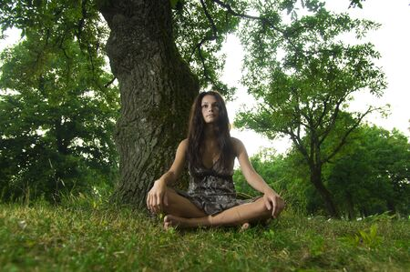 Beautiful young woman sitting under a tree. Taken in Lipica, Slovenia. Concept: teenagers and nature photo