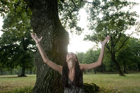 Beautiful young woman with arms raised sit under a tree. Taken in Lipica, Slovenia. Concept: teenagers and nature, nature love. photo
