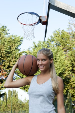 Young woman holding basketball at basketball court photo