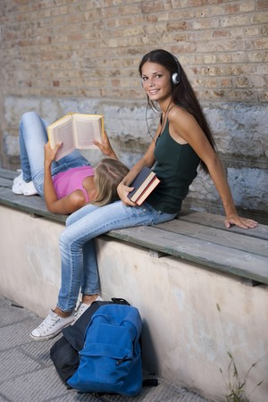 Teenage girls studying on a bench Stock Photo - 7505470