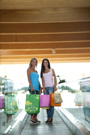 Beautiful teenage girls on escalator at shopping center Stock Photo - 7511607