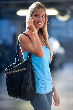 Young woman speaking on the phone while at an underground car park Stock Photo - 7511603
