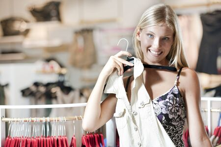Young woman trying dress on photo