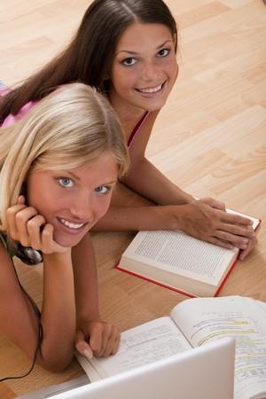 Happy teenage girls studying on the floor photo