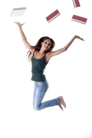 愉快的学生跳跃,投掷书外面。概念:学校结束