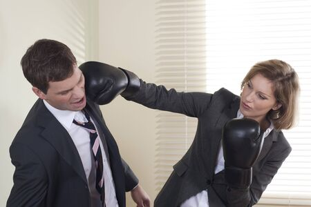 battle: Businessman and woman boxing in the office