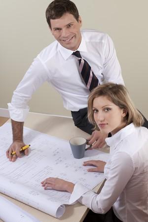 Businesspeople working on blueprints photo