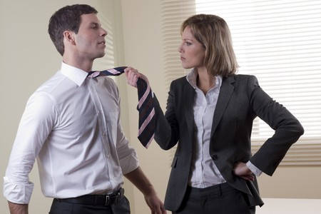 Business woman pullling his colleague from necktie photo