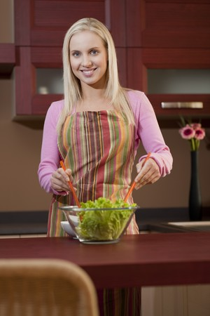 Happy young woman having fun in a kitchen preparing a vegetable salad. Stock Photo - 7801519