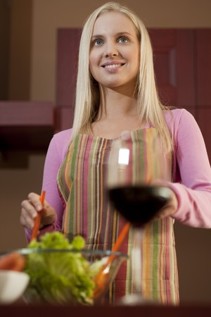 Young woman preparing salad, displaying a red glass of wine; selective focus photo