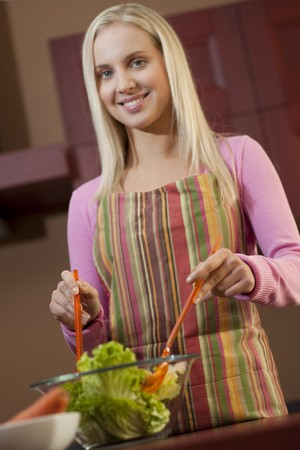 Happy young woman having fun in a kitchen preparing a vegetable salad. photo