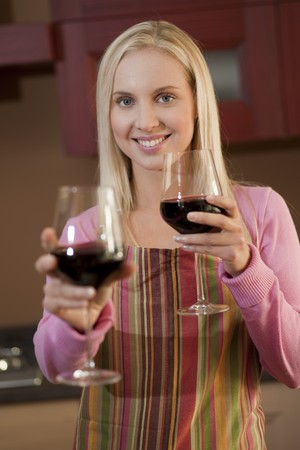 Young woman offering a glass of red wine in her kitchen photo