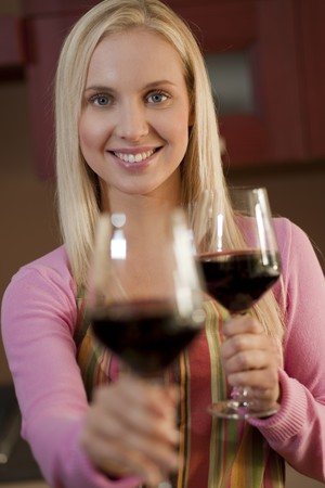 Young woman offering a glass of red wine in her kitchen Stock Photo - 7801508