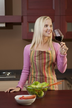 Young attractive woman tasting red wine before dinner Stock Photo - 7801524
