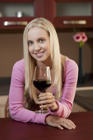 Young attractive woman tasting red wine before dinner photo