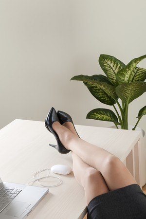 businesswoman legs: Close-up of businesswoman legs on the desk Stock Photo