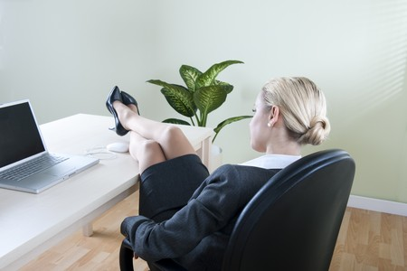 Relaxed businesswoman with legs on the desk photo