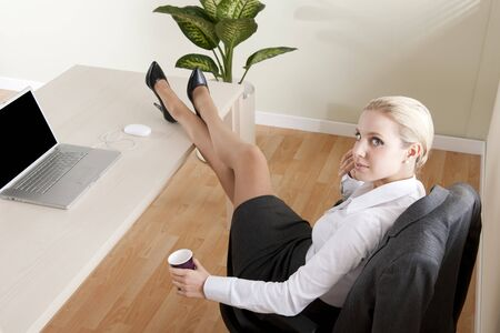 secretary skirt: Relaxed businesswoman with legs on the desk
