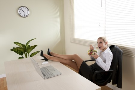 businesswoman skirt: Young businesswoman eating salad in her office
