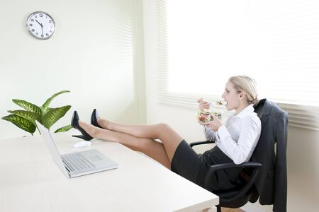 Young businesswoman eating salad in her office