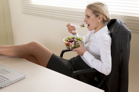 Young businesswoman eating salad in her office photo