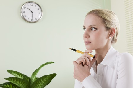 Pensive businesswoman with pen photo