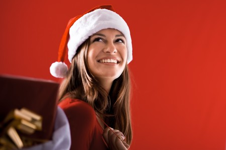 Smiling Santa Girl with gifts on red background Stock Photo - 7940948