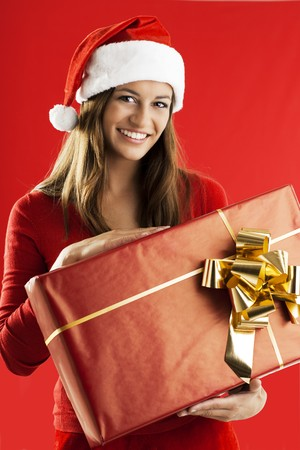 Santa Girl with a big present on red background photo