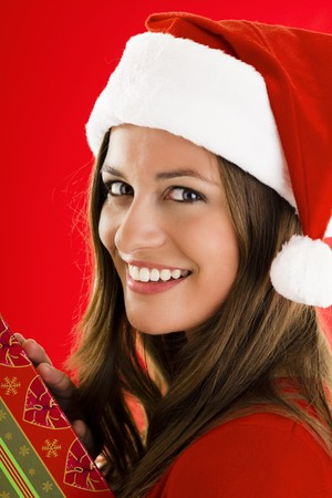 Portrait of a smiling Santa Girl with present photo