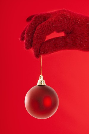 Hand holding red Christmas ornament on red background. photo