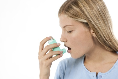 inhaling: Young woman using asthma inhaler Stock Photo