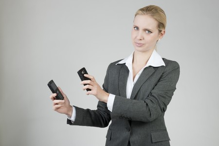 Businesswoman holding two mobile phones speaking each other photo