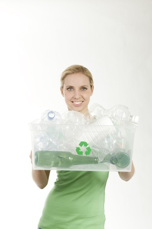 classifying: Happy young woman with recycling bin before classifying glass and plastic