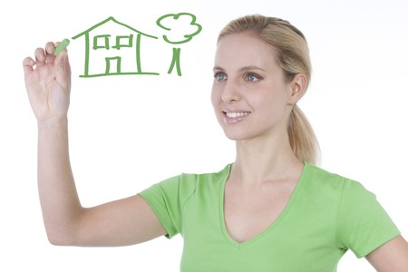 Young woman drawing house and tree on copy space photo