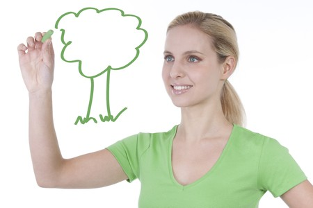 Young woman drawing a tree on copy space; concept: green living photo