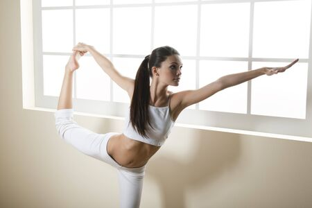 Young woman doing yoga or stretching, arm outstretched