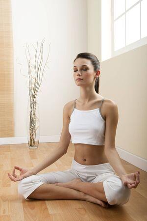 mujer meditando: Joven meditando sentado en posici�n de loto